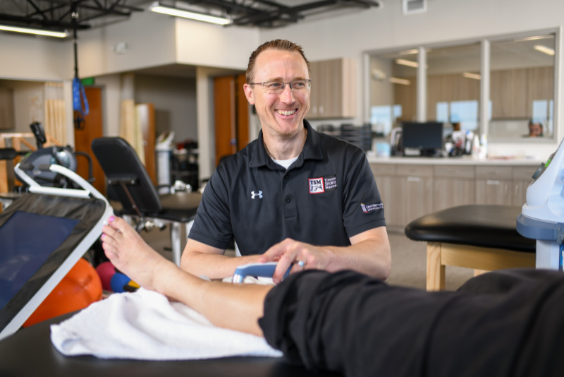 physical therapist performing therapy on patients lower leg