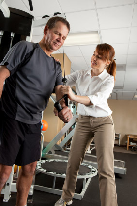 Physical therapist assisting man with shoulder therapy