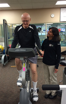Physical therapist assisting senior on an exercise bike