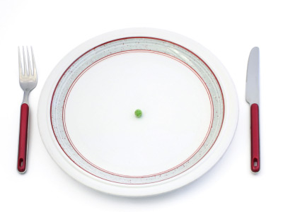 plate, fork and knife with one pea in the center of the plate